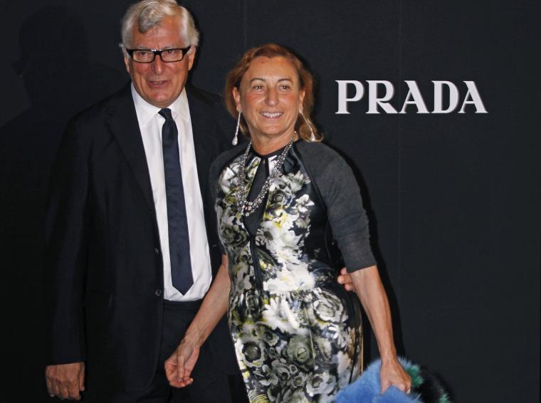 Italian fashion designer Miuccia Prada and her husband Patrizio Bertelli, also Prada's chief executive, walk past a Prada logo in 2011.