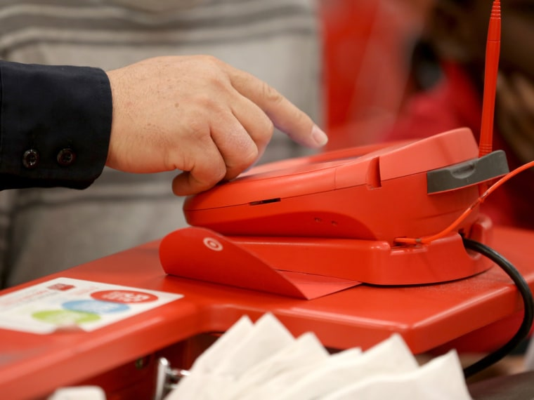 A customer uses a credit card scanner at a Target store. The retailer revealed Friday that the data breach that hit its customers over the heart of the holiday shopping season was almost twice as large as first revealed.