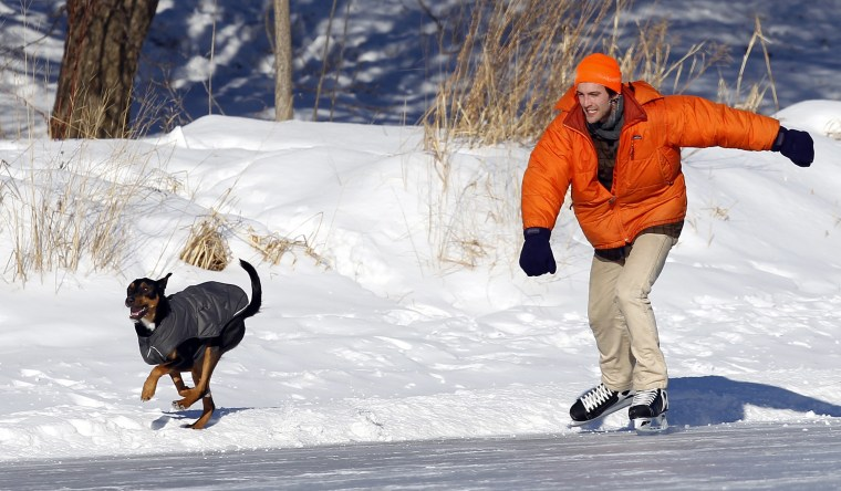 Cyril River races his dog, Aldo, as he skates around Lake of the Isles in Minneapolis, January 8, 2014. A deadly blast of arctic air shattered decades...
