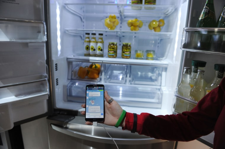 A LG representative shows a smartphone with Home Chat in front of a LG smart refrigerator on the final day of the 2014 International CES, January 10, ...