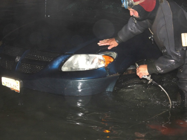 Rescue diver Travis Preston, a Jonesboro, Maine, firefighter, hooks up a minivan in the water on the boat ramp at the scene of a double fatal accident Tuesday evening July 23, 2013, in Roque Bluffs, Maine.