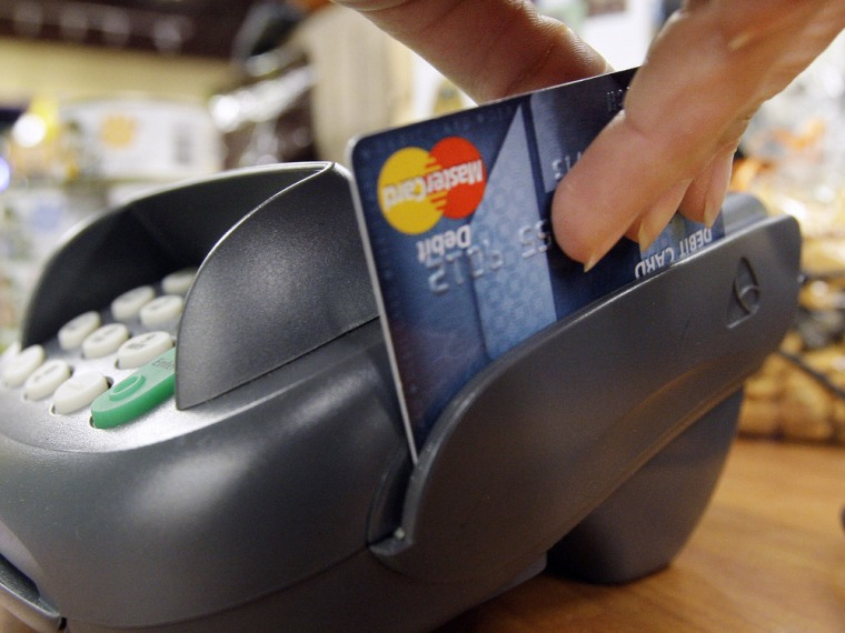 FILE - In this Nov. 2, 2009 file photo, a customer swipes a MasterCard debit card through a machine while checking-out at a shop in Seattle. Congress ...