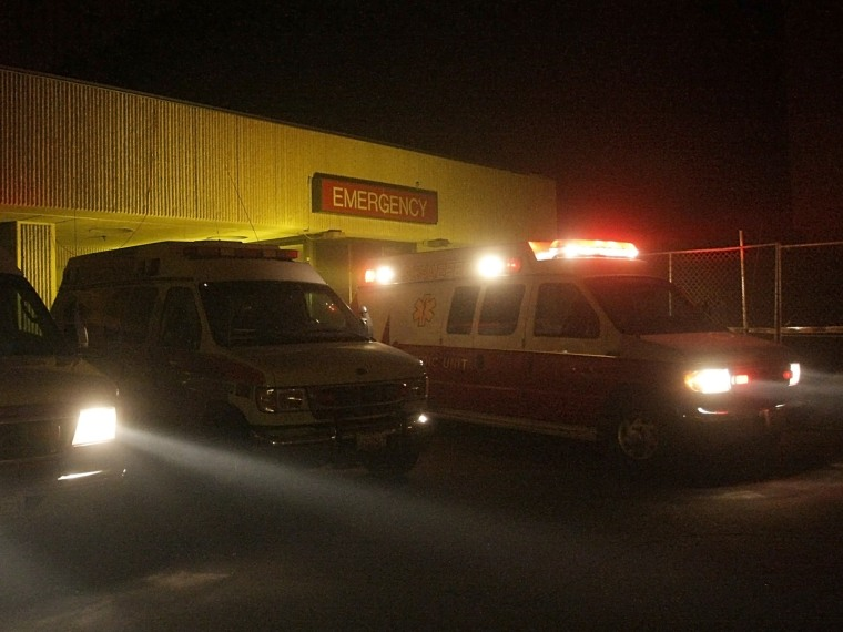 FILE: Ambulances line up at the ambulance entrance of the Olive View Hospital emergency room during a wind-driven brush fire in Los Angeles, Friday, N...