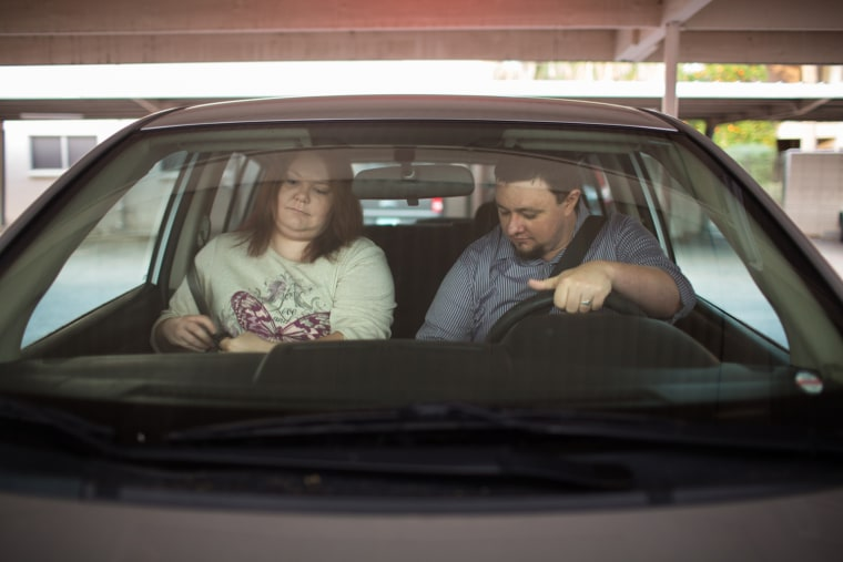 Ben and Erika Trowell leave home for work in the car they share in Phoenix, Ariz.
