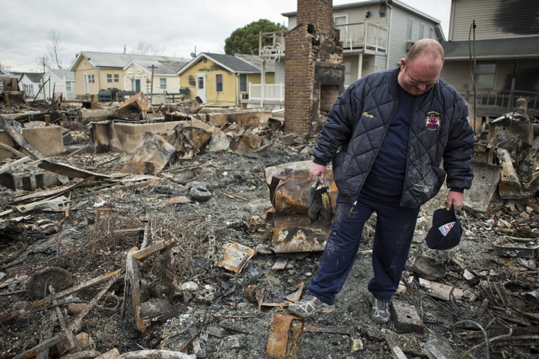 Kieran Burke surveys the burned-out remains of his Breezy Point, N.Y., home on Wednesday, Oct. 31, 2012. Breezy Point residents returned to their deva...