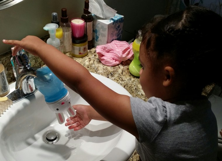 Daddy to the rescue: The much-loved Bunny sippy cup is repurposed to make hand washing more fun for 3-year-old Emiko.