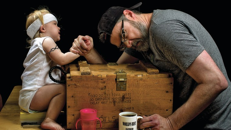 Image: Dad and daughter arm wrestle