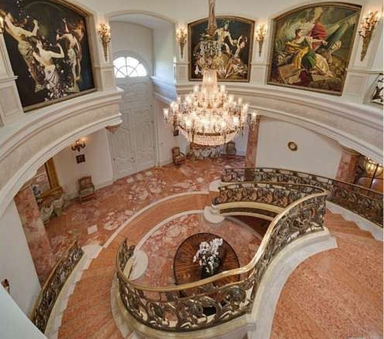 The entry is highlighted by a chandelier and pink marble floors.