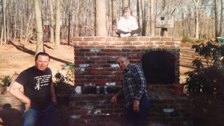 """That's me sitting on top of the grill my dad built. He built our whole house and this was our backyard. My dad is on the left and my grandma's friend Joe is on the right."""