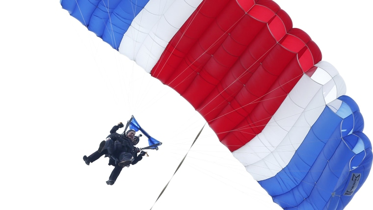 Former President George H.W. Bush, strapped to Sgt. 1st Class Mike Elliott, a retired member of the Army's Golden Knights parachute team, floats to the ground during a tandem parachute jump near Bush's summer home in Kennebunkport, Maine, on Thursday in celebration of his 90th birthday.
