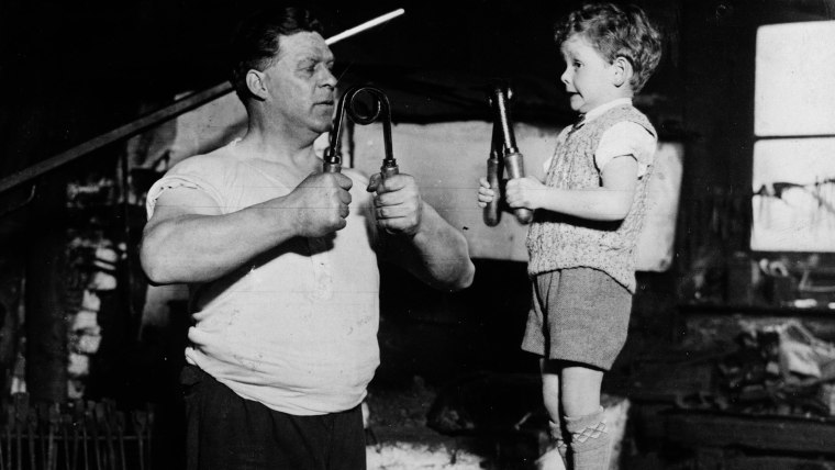 Image: A young boy and his father flex their muscles