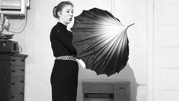 Image: A woman opens an umbrella indoors