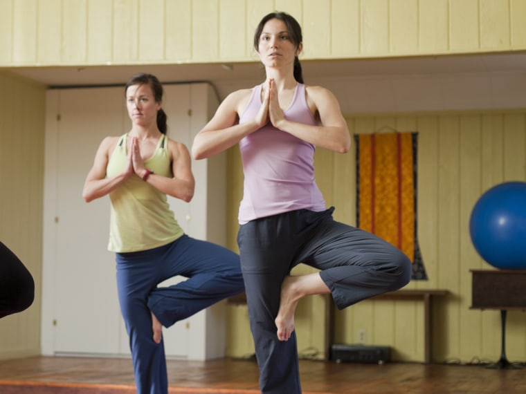 An older woman leads yoga in a small studio for two younger women.