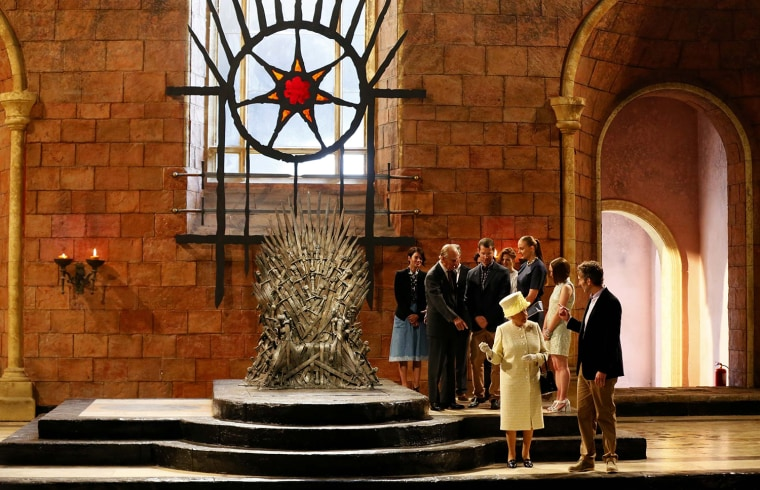 Britain's Queen Elizabeth and Prince Philip talk with members of the cast on the set of the television show Game of Thrones in the Titanic Quarter of ...