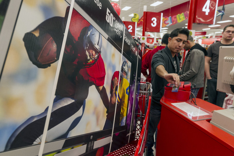 Consumer Ash Gan, 19, swipes his credit card to par for a television doorbuster deal at Target store in Burbank, Calif., on Thursday, Nov. 22, 2012. W...
