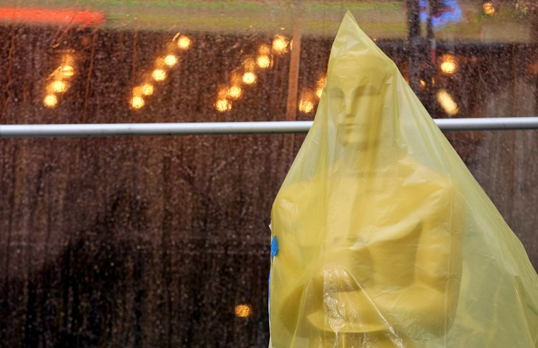 An Oscar statue covered in plastic stands on the red carpet Friday as preparations are made during rainy weather for the 86th Academy Awards in Los An...