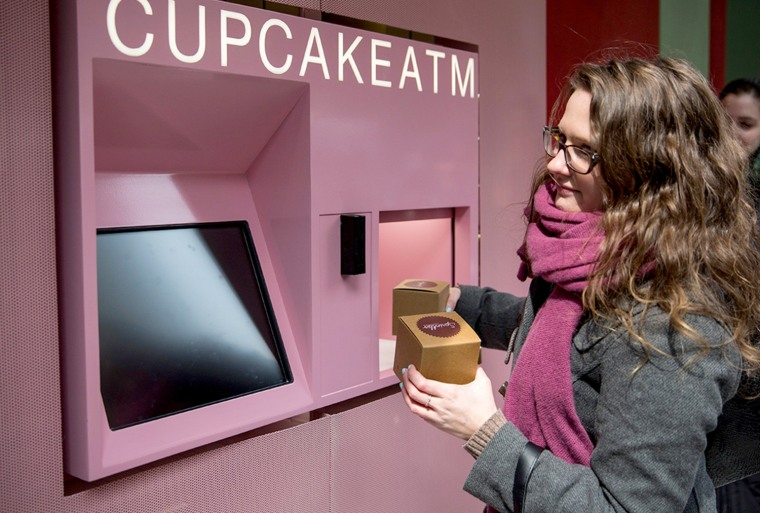 """A woman takes her order of cupcakes after using a """"Cupcake ATM"""" created by Sprinkles bakery on March 25, 2014 in New York Ci..."""