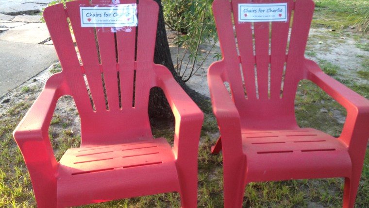 """Two red Adirondack chairs have signs that say """"Chairs for Charlie."""" They are for Charlie George, who is battling leukemia, to use if he gets tired while strolling the neighborhood."""