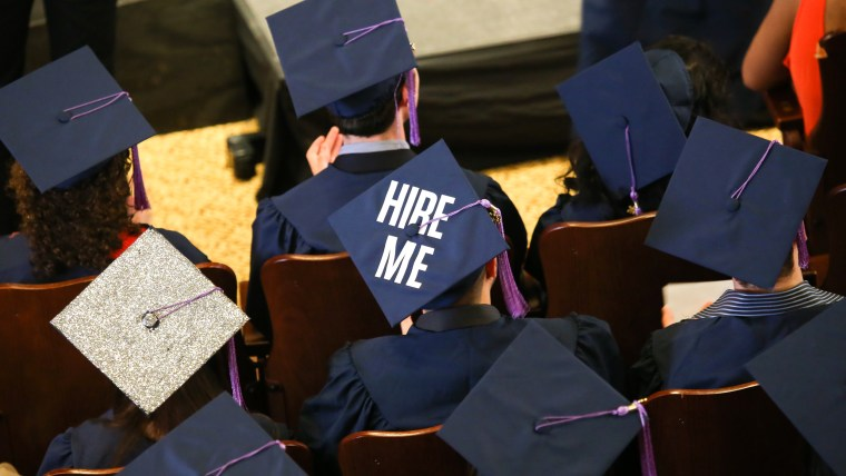 A student from the Syracuse University School of Architecture wears the words 'HIRE ME' on his graduation cap during the commencement ceremony.