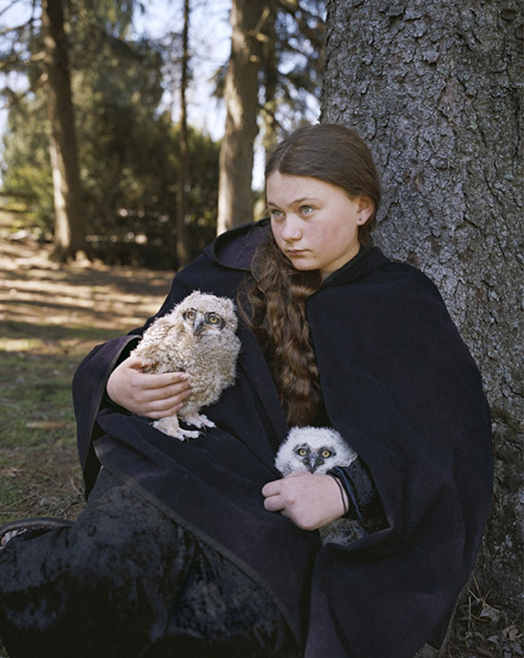 Image: Girl holding two owls.