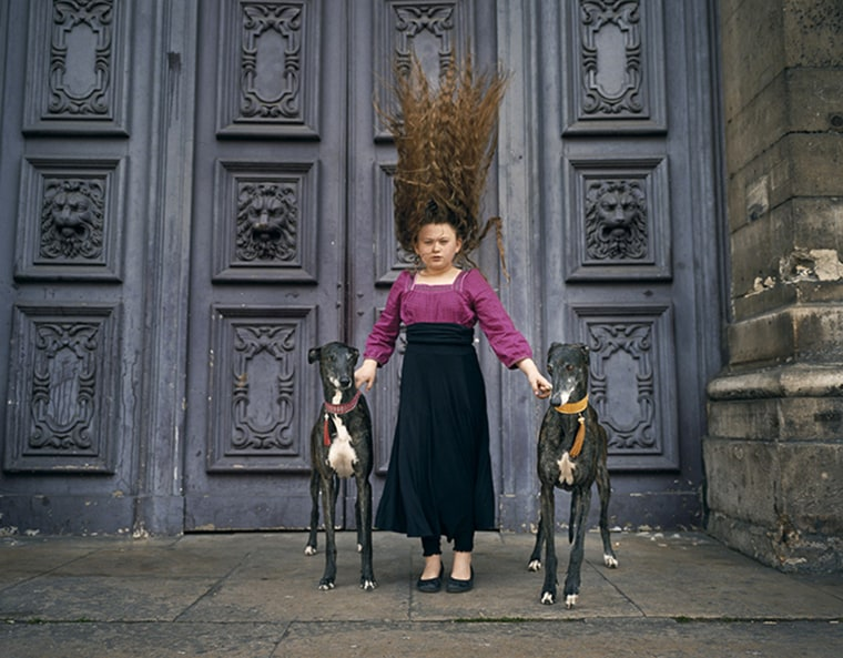 Image: A girl and two greyhounds.