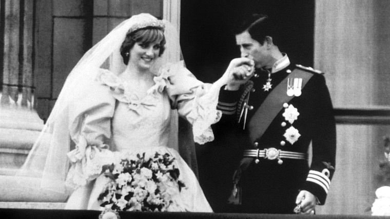 Image: Charles, Prince of Wales, kisses his new bride, Princess Diana's hand on the balcony of Buckingham Palace.