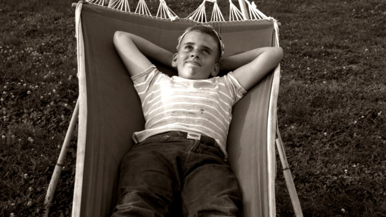 Image: Boy relaxing in a suburban backyard hammock