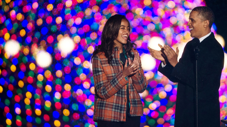 President Barack Obama and his daughter Malia applaud together after lighting the National Christmas Tree on Dec. 6, 2013.