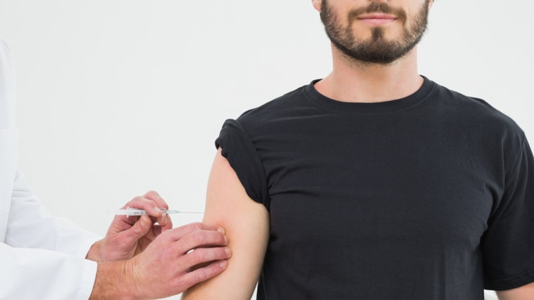 Close-up of hands injecting a young male patient's arm over white background; Shutterstock ID 167537753; PO: TODAY.com