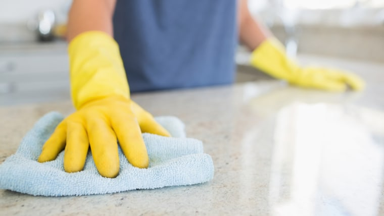 Woman cleaning the counter  in the kitchen; Shutterstock ID 117715075; PO: today.com