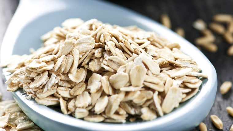 Rolled oats heaped on a spoon and whole oat groats
