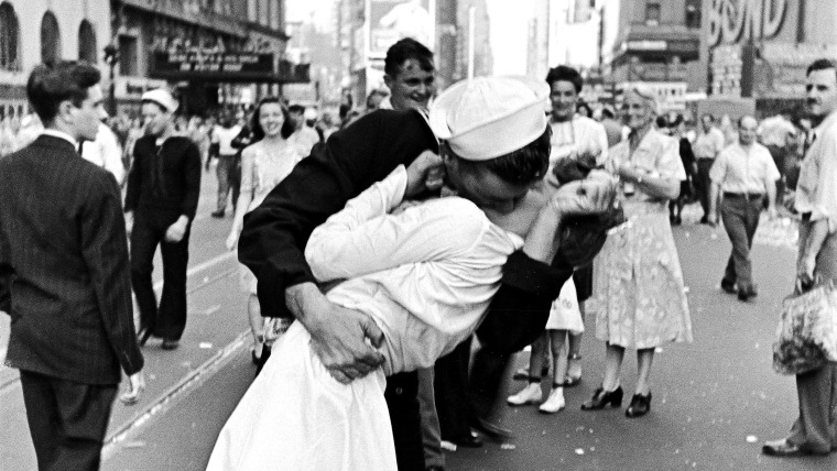 As pedestrians watch, an American sailor passionately kisses a white-uniformed nurse in Times Square to celebrate the long awaited-victory over Japan....