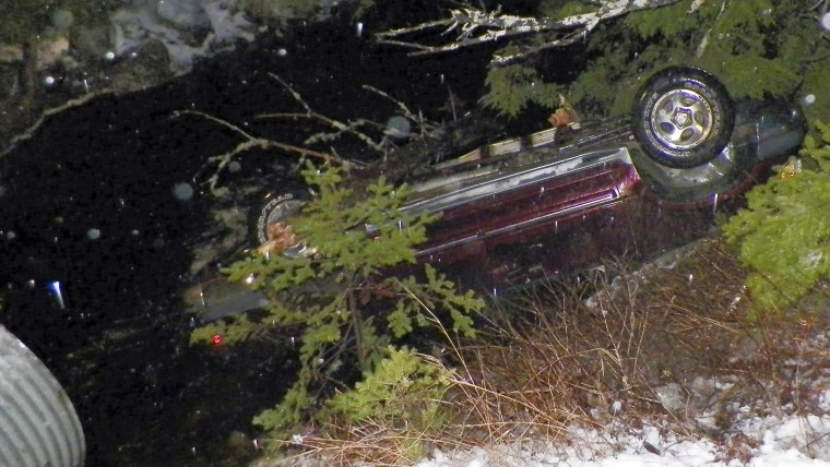 An SUV rests upside down in water alongside Route 6 in Kossuth Township, Maine, after Stephen McGouldrick lost control of it on the icy road. Police s...