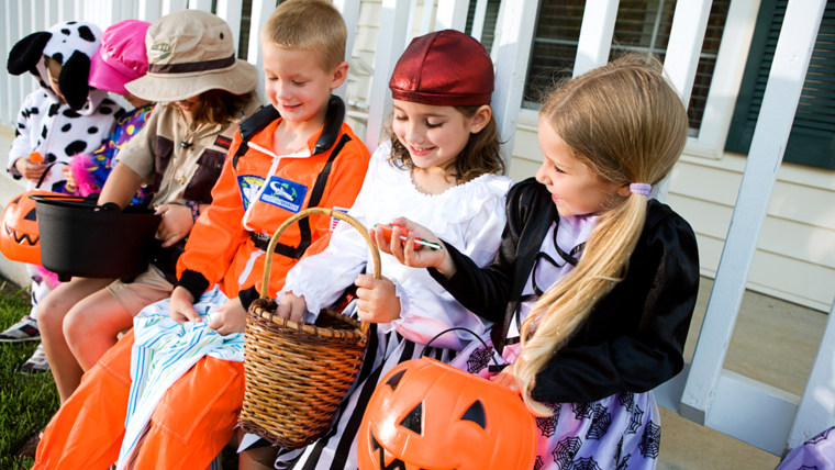 Halloween: Kids Sit On Porch And Look At Halloween Candy; Shutterstock ID 210749683; PO: TODAY.com