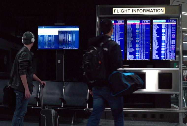 Image: Travelers check the status of flights at Boston's Logan International Airport
