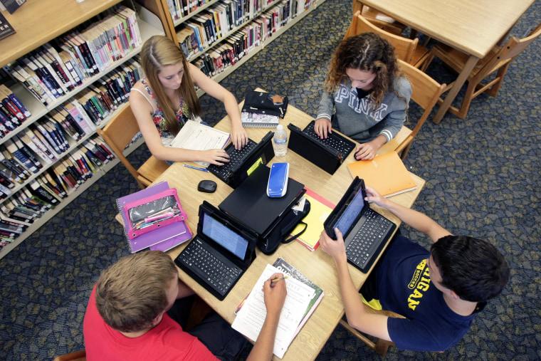 Clark Mjelstad, bottom left, Autumn Gossett, Jackie Harmon and Alex Kramlich work on their tablets on Sept. 4, 2013, in the library at Fargo North Hig...