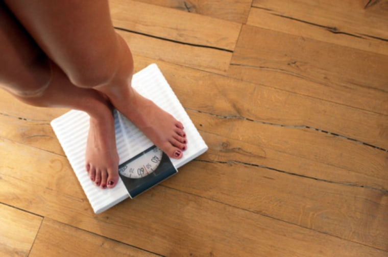 Woman standing on weighing scales, elevated view Getty Images stock, msnbc stock photography, Control, Aspirations, Accuracy, Horizontal, Indoors, Low...