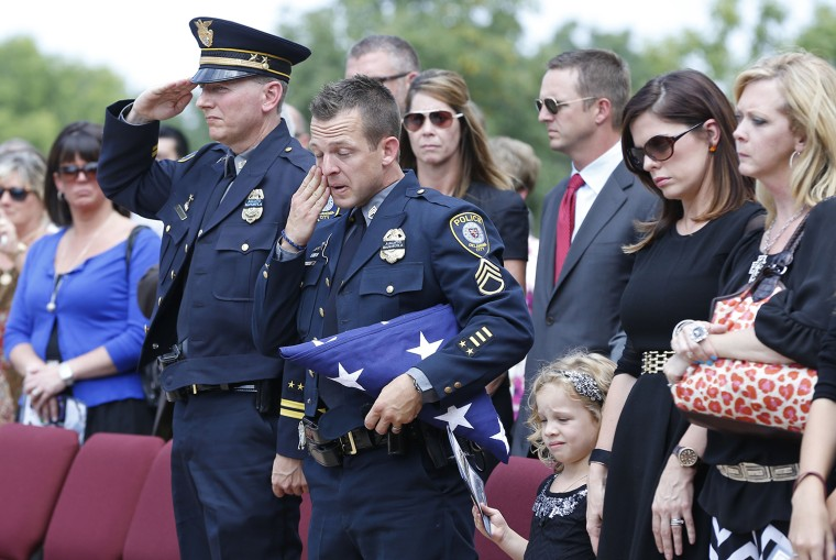 Oklahoma City police officer Sgt. Ryan Stark, center, wipes a tear from his eye following funeral services for his canine partner, K-9 Kye, in Oklahom...