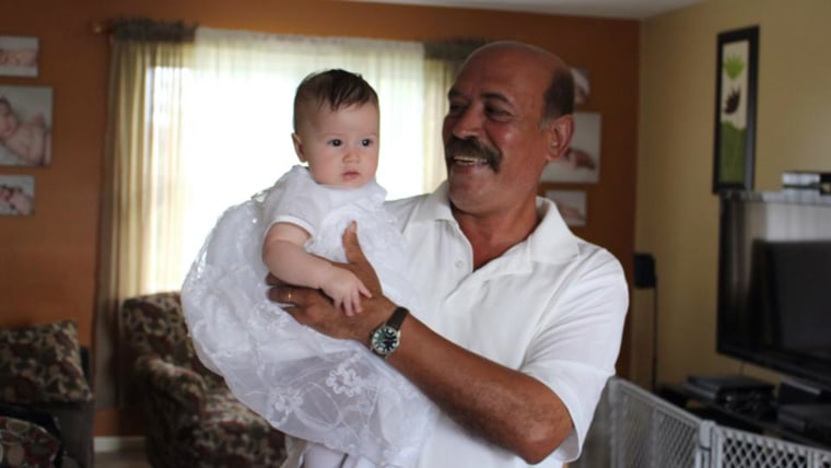Gaga (grandfather) holding his newest granddaughter, Eva, who was born in April, at her baptism this weekend.