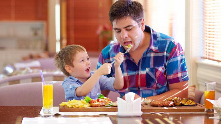 boy feeding father