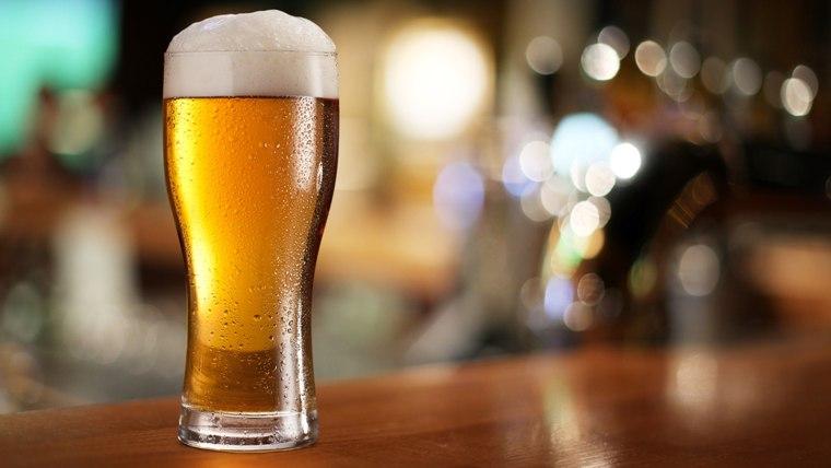 Glass of light beer on a dark pub.; Shutterstock ID 120711982; PO: today.com