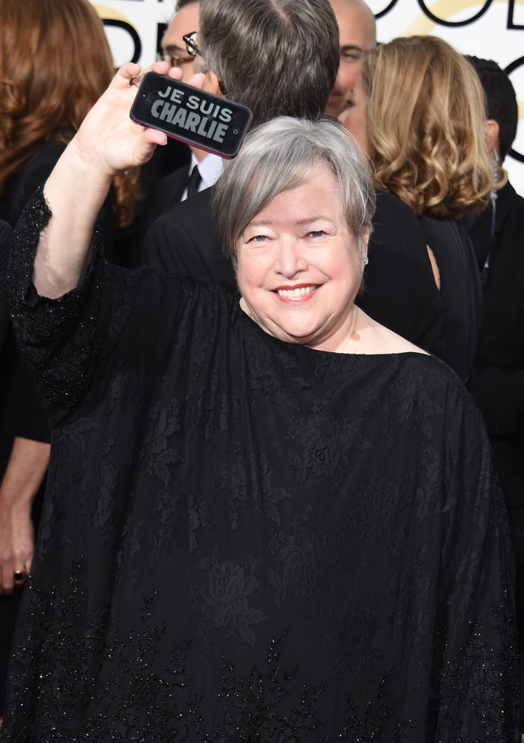 """Image: Actress Kathy Bates shows a """"Je suis Charlie"""" on her phone as she arrives on the red carpet for the 72nd Annual Golden Globe Awards, January 11, 2015 at the Beverly Hilton Hotel in Beverly Hills, California."""