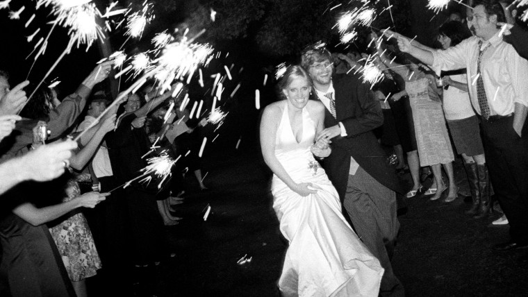 Carissa and Chris Ray exit their 2006 wedding through a tunnel of family and friends.