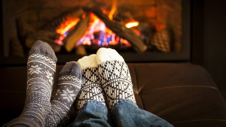 Feet in wool socks warming by cozy fire; Shutterstock ID 142464652; PO: today.com