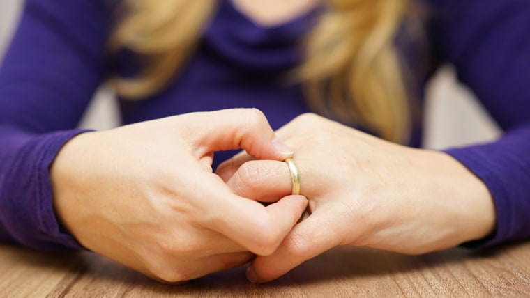 Image: woman is taking off the wedding ring