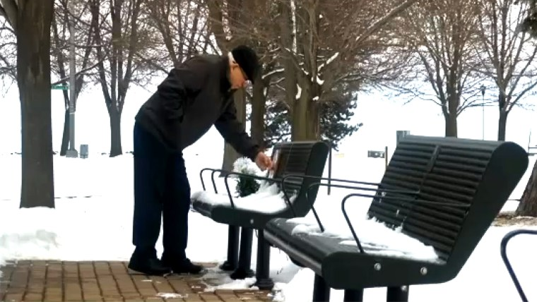 Elderly man pays respect to his late wife