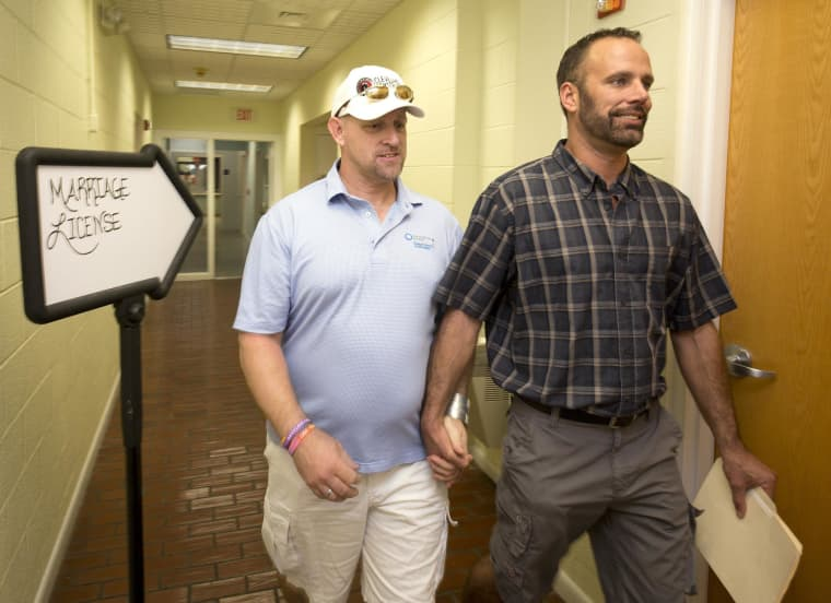 Image:  William Lee Jones (L) and Aaron Huntsman leave the Monroe County Clerk of the Court's office after completing a marriage license application on Jan. 2, in Key West, Florida.
