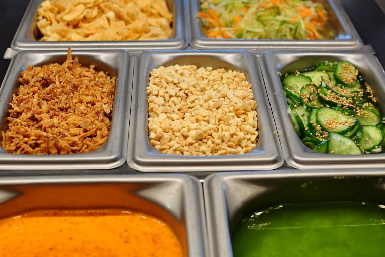 The sauce and condiment bar featuring traditional and Chinese inspired toppings at the Panda Express Innovation Kitchen
