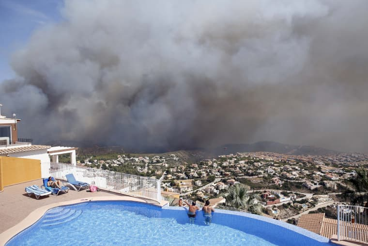 Image: Two men look at a wildfire from a swimming pool