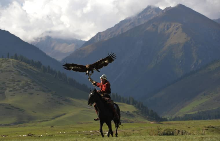 Image: A mounted Kyrgyz berkutchi holds his golden eagle during the World Nomad Games 2016